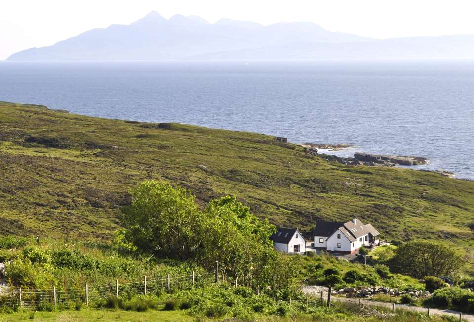 Shore Cottage and Pier House with the Isle of Rhum in the background